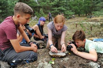 Jugendliche beim Fotografieren einer Zauneidechse